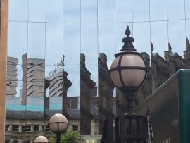 Moderne Gebäude spiegeln sich in einer Fensterfront.